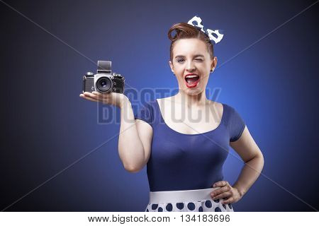 Pin Up girl holding a vintage camera on blue background