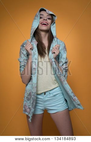 Gorgeous beautiful smiling young woman in casual hoodie and green shorts on orange background