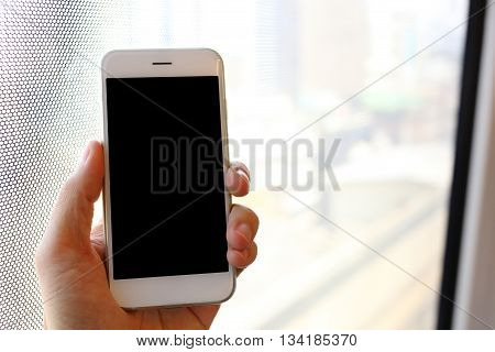 Hand holding white color smartphone in train