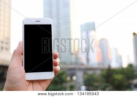 Hand holding white smartphone with cityscape background