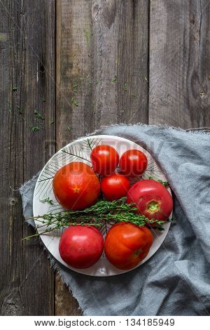 Heirloom tomatoes and fresh thyme springs on plate, rustic wooden background and copy space for text