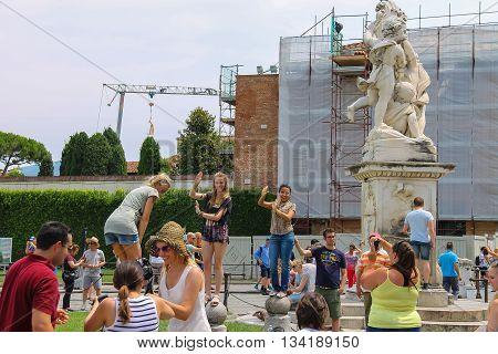 Pisa Italy - June 29 2015: Tourists near the fountain with angels on Piazza del Duomo. Province Pisa Tuscany region of Italy