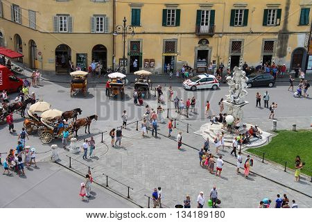 Pisa Italy - June 29 2015: Tourists near the fountain with angels on Piazza del Duomo. View from Leaning Tower