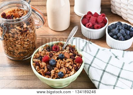A breakfast of homemade granola cereal and fresh picked berries. A bottle of milk and bowls of raspberries and blueberries on a wood table.