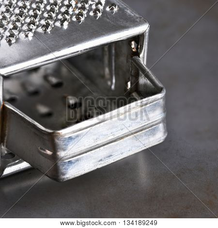 Closeup of a metal cheese grater on a baking sheet.