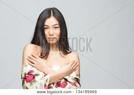 Portrait of beautiful fashion asian lady in spring or summer dress posing in studio. Brunette woman with her arms crossed or folded isolated on grey background.