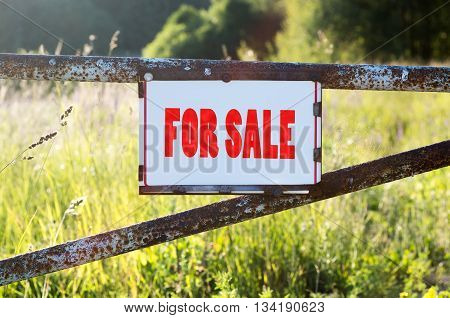 Sign For Sale on a metal gate on the dirt road
