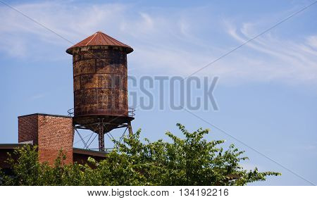 An industrial water tower stands against blue sky