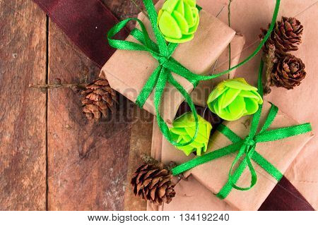 Green presents wrapped in natural paper on old wooden background.
