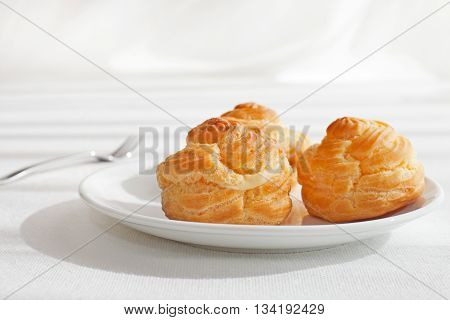 Profiteroles, choux with a custard cream, creme anglaise, whipped cream, dessert on a white plate Copy space