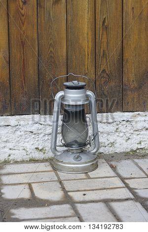 kerosene oil lamp near wood wall and white foundation close up