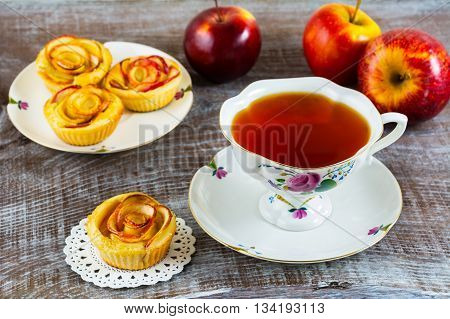 Homemade Apple rose cake and cup of tea. Homemade rose apple cake. Sweet gourmet cupcakes. Homemade sweet apple dessert. Breakfast tea and apple pastry.