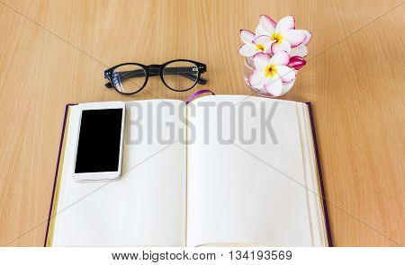 Plumeria or frangipani flowers in glass with smartphone on blank note bookempty diary with frangipani or plumeria flowers and blurred eyeglassesblank page diary on wooden table