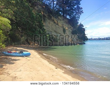 Kayaking expedition to a sandy beach on Auckland's North Shore. Auckland CBD is just behind the cliff, on the other side of the Waitemata Harbour.