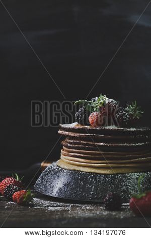 Chocolate pancakes in rusty pan with organic fruits like strawberries blackberries and castor sugar on old wooden table