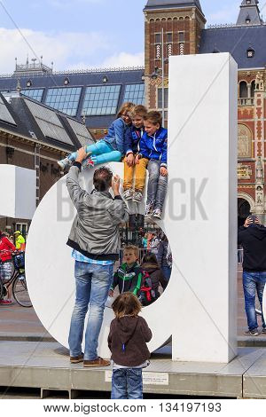 AMSTERDAM, NETHERLANDS - MAY 9, 2013: Unknown man wants to take a picture of his children on one of the letters of the inscription