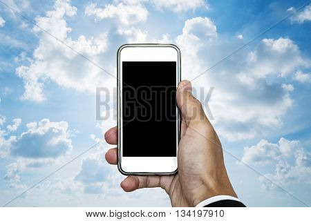 Hand holding mobile phone with blank space on screen, on blue sky with white clouds and bright light