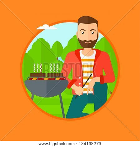 A hipster man sitting next to barbecue grill in the park. Man cooking meat on the barbecue grill. Man having a barbecue party. Vector flat design illustration in the circle isolated on background.