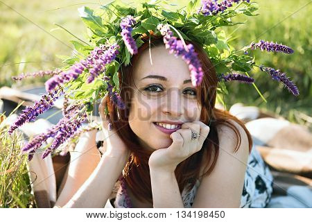 girl with a wreath on his head lying on the grass