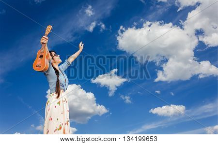 Asian Women Smiling Happily Holding Ukulele And Raise Two Arms Embrace Blue Summer Sky With Puffy Cl