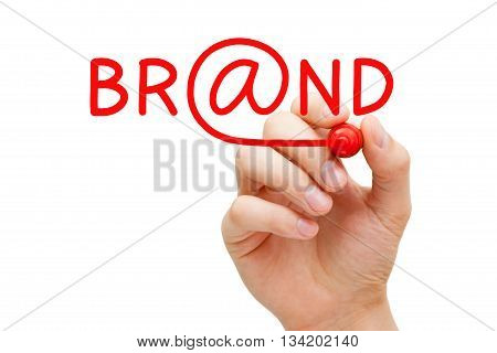 Hand writing Brand with red marker on transparent wipe board. Online branding concept.