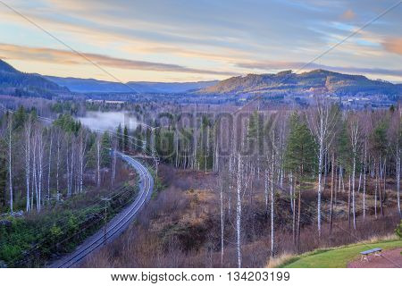 evening forest mountain landscape with mist and railroad