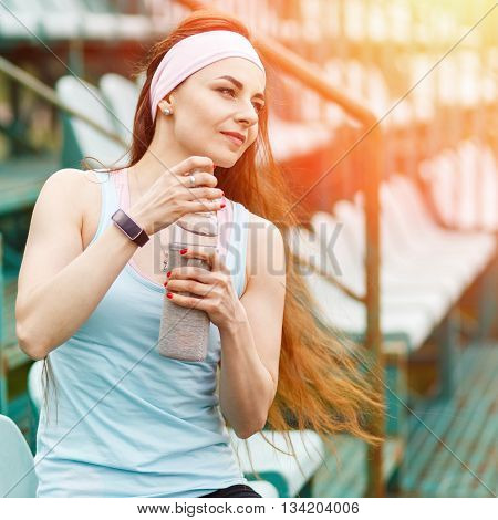 Young Smiling Sportswoman With Bottle Of Water
