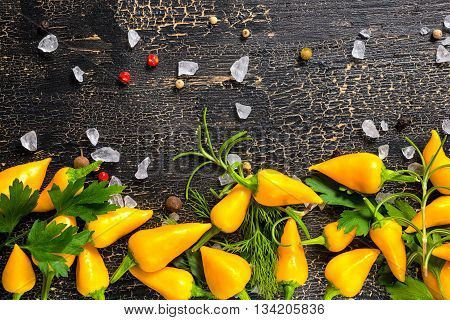 Flat Lay Of Decorative Yellow Spices, Dry Peppers, Sea Salt, Different Greenery On Cracks Black Food