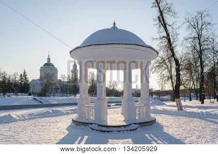 White arbor with the columns standing on the shore of frozen river in winter