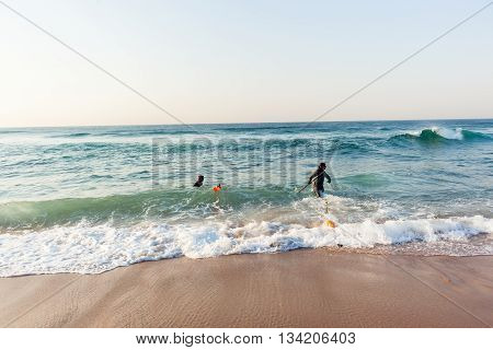 Divers spear fishing guns goggles line buoy beach entry swim into ocean