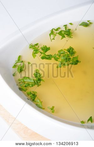 Yellow broth with herbs in a white bowl