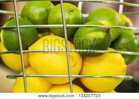 Lemons and green limes in the metal basket. Close up fruit scene. Healthy food. Refreshing ingredients. Source of vitamins.