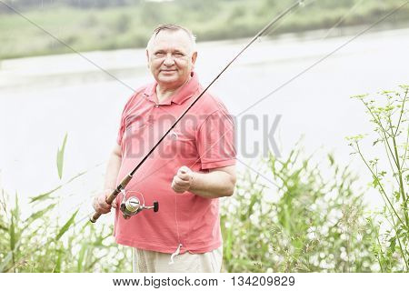 Portrait of smiling middle aged man wearing polo shirt, angling with rod and spinning reel in rain on summer lake - fishing concept