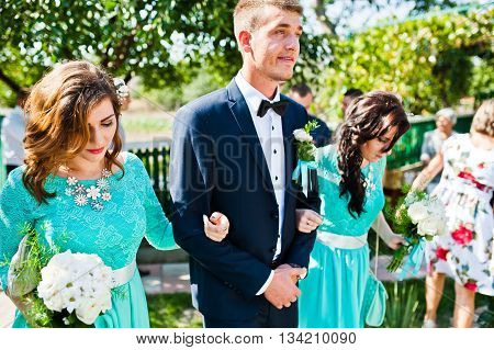 Bridesmaid holding groom under arms at wedding