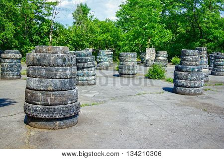 Abandoned paintball playground with barricades made of old tires with paint marks after fights