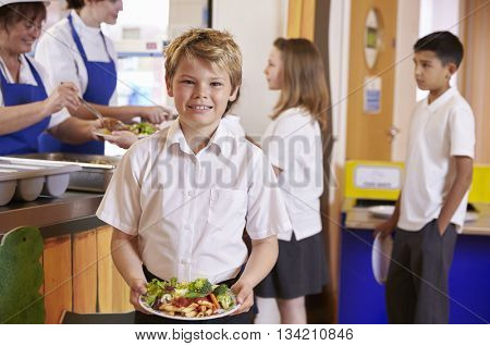 Blonde haired boy holding plate of food in school cafeteria