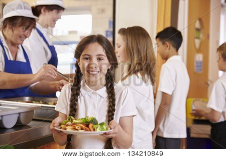Girl with plaits holding plate of food in school cafeteria