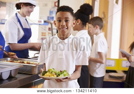 Mixed race boy holding a plate of food in a school cafeteria