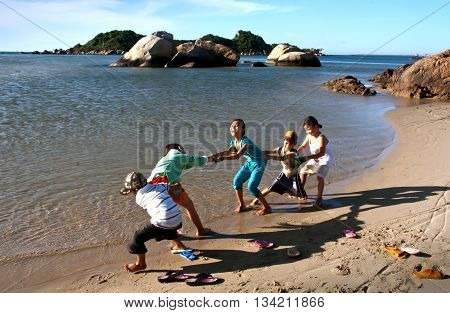 QUANG BINH, Vietnam, April 11, 2016 the group of children, Quang Binh waters, playing tug of war, close to the coast, on a sunny day
