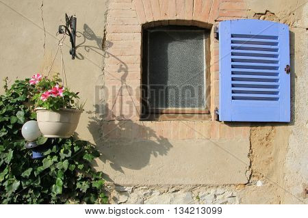 Hanging flowerpot next to a small window with blue shutter