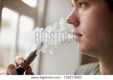 Close Up Of Man Using Vapourizer As Smoking Alternative