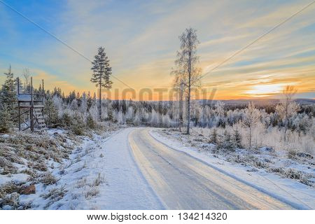 hunt tower and road with ice and snow with trees during sunset