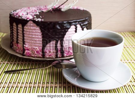 Biscuit cake with fruit souffle decorated with chocolate and cup of tea.