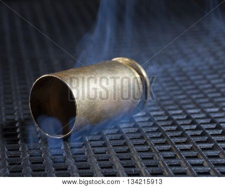 Empty brass casing from a handgun with smoke rising