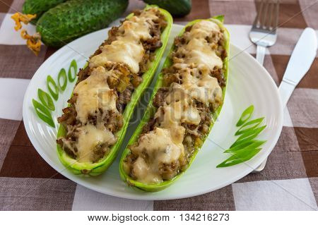 Baked stuffed zucchini and vegetables on a white plate close up. Dietary lunch.