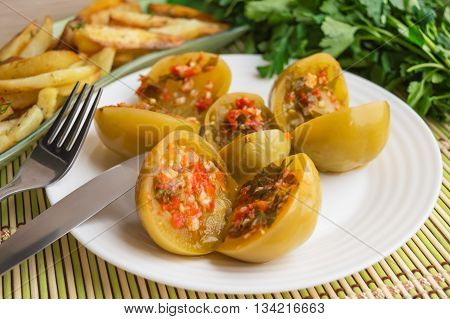 Spicy green tomatoes stuffed with parsley hot pepper garlic on a white plate