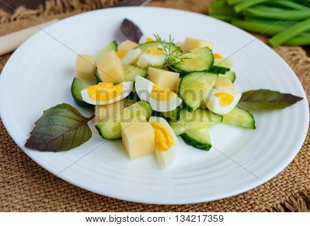Light Italian Spring salad with fresh cucumber quail eggs mozzarella olive oil on a white plate on a wooden background. Dietary meal