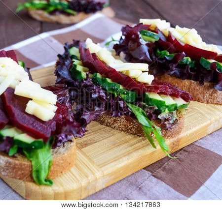 Dietary vitamin sandwiches with lettuce leaves cucumber beet and cheese on rye bread. Close-up.
