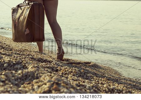 Barefoot woman walking down the beach holding a suitcase