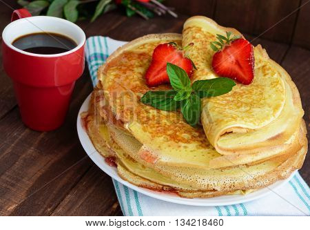 Pile of golden pancakes with strawberries and strawberry jam decorative sprig of mint. Close-up